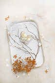 Old tin decorated with twigs, lace and butterfly made from mother-of-pearl buttons