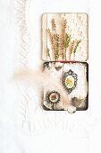 Old tin decorated with birch bark, brooches, feather, sprigs of heather and fabric