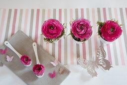 Romantic arrangement of deep pink ranunculus and butterflies