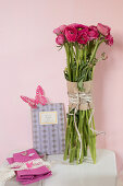 Bunch of deep pink ranunculus and romantic butterfly decorations