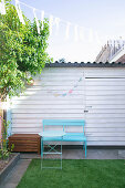 Pale blue bench and folding table providing a splash of colour in a courtyard garden