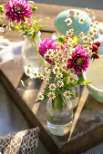 Garden flowers in glass bottles as decoration for picnic on lake