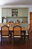 Grey-green dresser and cane-backed chairs around dining table in kitchen-dining room