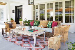 Rattan sofa and wicker chairs in seating area on veranda