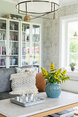 Blue vase of yellow loosestrife and glass-fronted bookcases in living room
