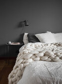 Chunky knitted blanket on double bed against grey bedroom wall