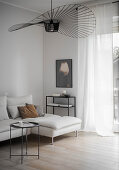 Fan-shaped designer lamp and white chaise couch in living room