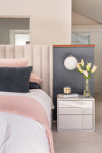 Half-height partition wall behind bed in pastel bedroom