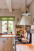 Gas cooker in cosy country-house kitchen with ceiling beams