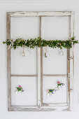 Old window decorated with garland of box, Easter eggs and suspended vases hung on wall