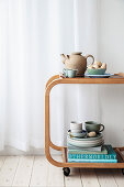 Crockery in sage green and natural shades on minimalist serving trolley