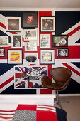 Vintage leather chair next to posters on wall covered with Union-flag wallpaper