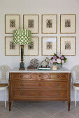Table lamp on antique chest of drawers below etchings