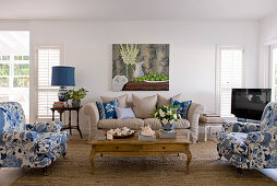 Upholstered furnishings in white, blue and ecru around coffee table in living room