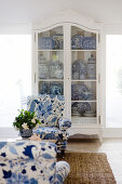 Blue-and-white armchair in front of white, antique cupboard