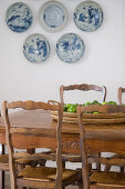 Rustic wooden table and chairs in front of decorative wall plates on white wall