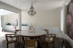 Table with marble top and chairs next to floral artwork in dining area