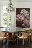 Table with marble top and chairs in front of floral artwork in dining area