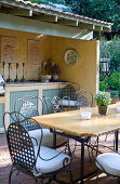Roofed outdoor kitchen counter on terrace in vintage country-house style