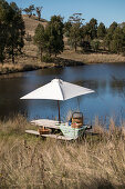 Picnic on rustic wooden table below parasol on lake shore