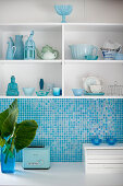 White and blue kitchen with splashback of sky-blue mosaic tiles below shelves