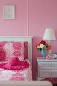 Feminines Schlafzimmer in Rosa mit weißem Holzbett und weißen Nachtschränkchen