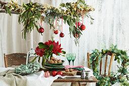 Blätterkränze und Ast dekoriert mit Blätterzweigen und Kugeln als Weihnachtsdeko