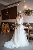 Bride wearing white wedding dress with train in interior with industrial ambiance