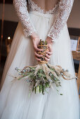 Bride holding bridal bouquet behind back