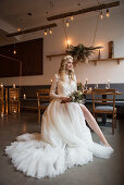 Bride wearing white wedding dress with train in vintage-style restaurant