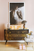 Painting above dark chest of drawers with feminine Christmas decorations
