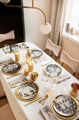 Portrait plates on festively set table in gold and white