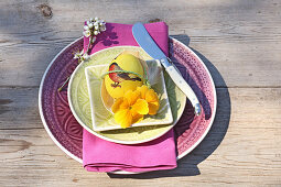 Easter egg with bird motif and yellow primula on purple place setting