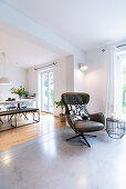 Leather armchair in bright living room with view into dining room