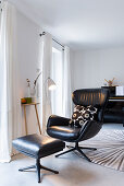Comfortable leather armchair with footstool in living room