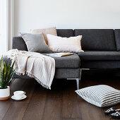 Kissen, Teetasse und Bogenhanf vorm grauen Sofa mit Plaid