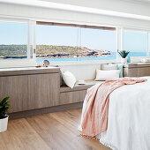 Horizontales Panoramafenster und Sideboard mit Bank im Schlafzimmer