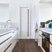 Moderne Küche mit weißen Fronten und Speisekammer