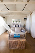Wicker basket in front of wicker sofa in summery bedroom