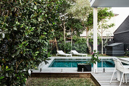 Swimming pool surrounded by wooden deck in garden