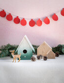 Winter arrangement of nesting box, fir cones, reindeer figurine and garland