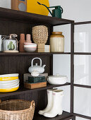 Baskets, crockery, wellington boots and ornaments in dark display cabinet