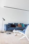 Blue, Scandinavian-style sofa in living room with wooden floor