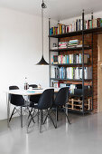Black shell chairs at dining table and bookcase against brick wall