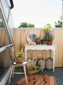 Accessories on old chair and console table on sunny inverted dormer roof terrace