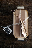 Wrapped gift decorated with golden leaf and lace ribbon on tray
