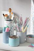 Tin cans covered with pastel paper on desk