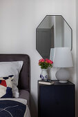 Ranunculus in vase with face on bedside cabinet in bedroom