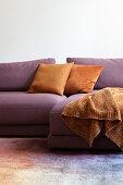 Orange blanket and scatter cushions on purple sofa on multicoloured rug