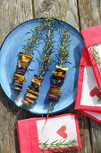 Colourful potatoes grilled on sprigs of rosemary and decorated napkins